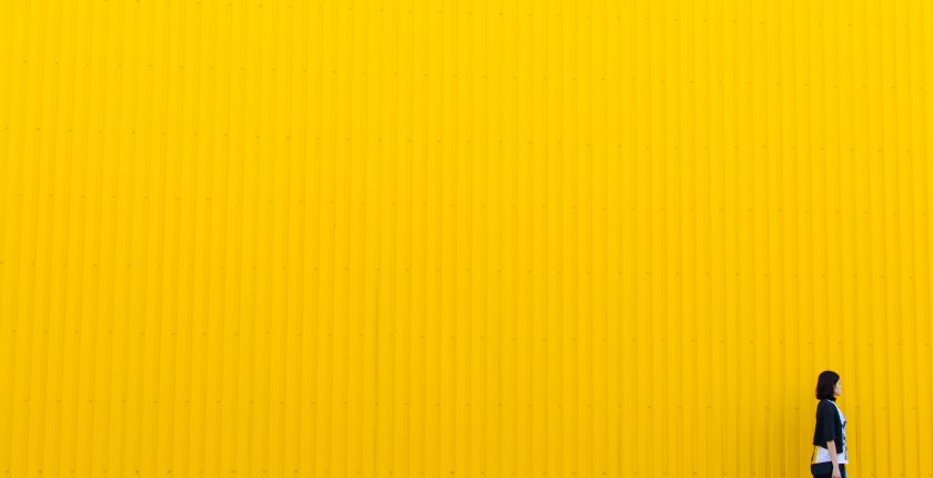 Girl walking in front of yellow wall